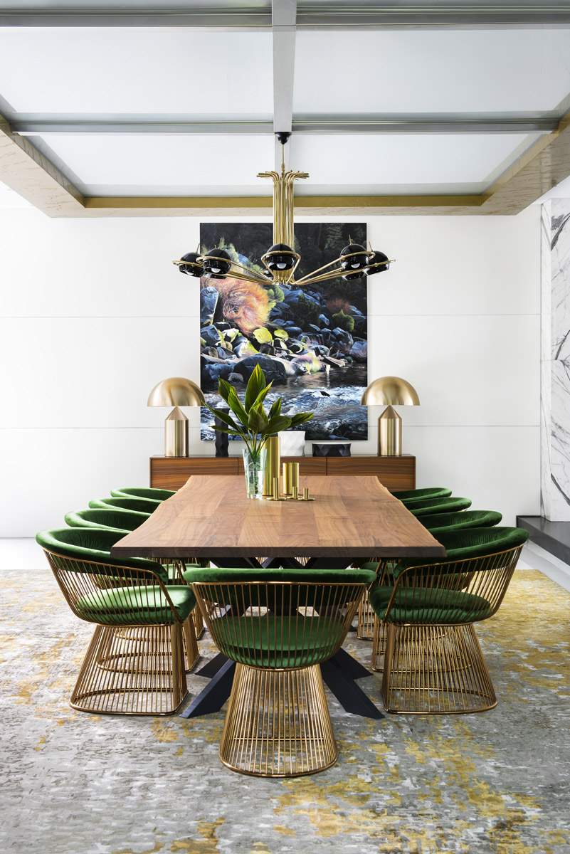 wooden dining table with gold and green chairs on a silver rug with paining on the wall