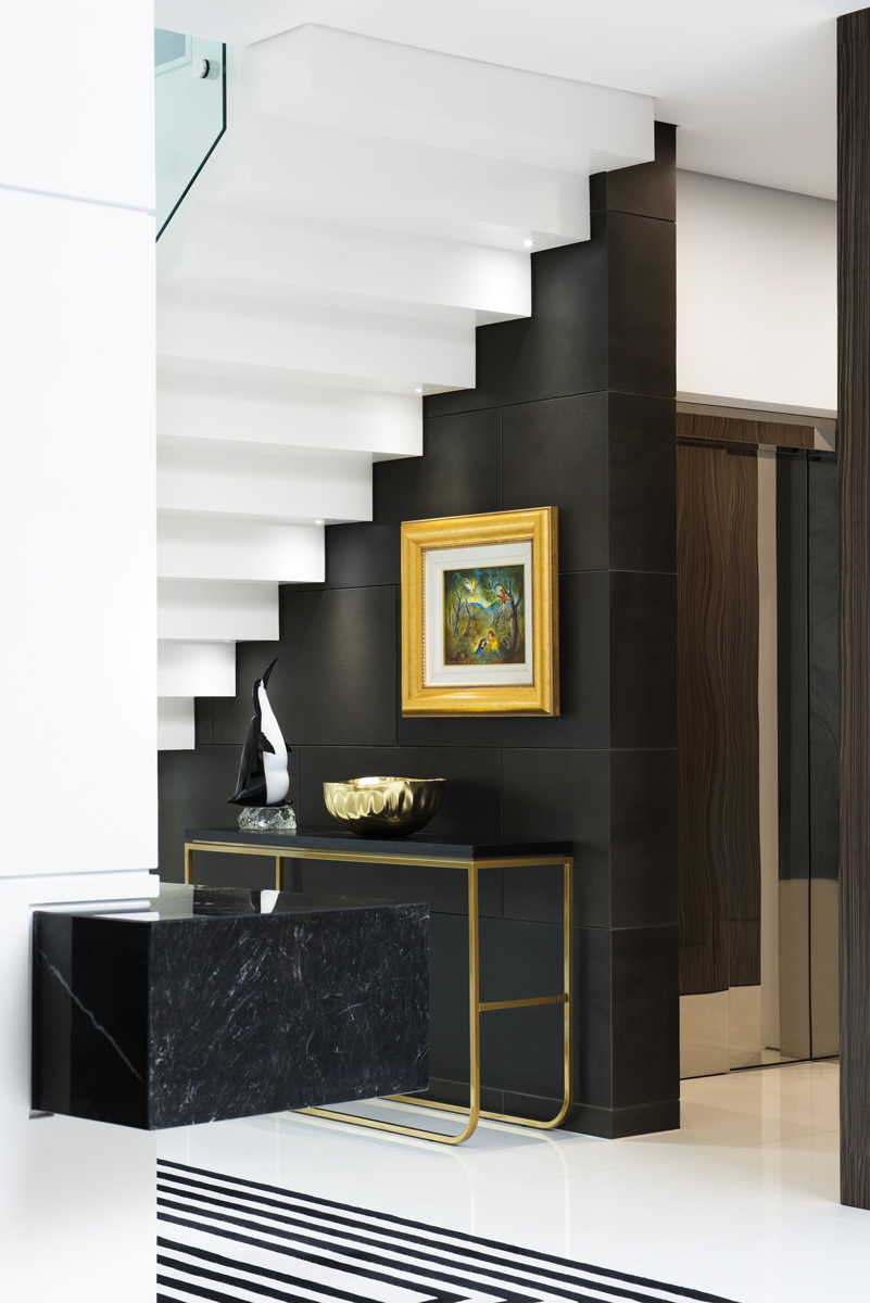black wall with gold framed pictures under white staircase