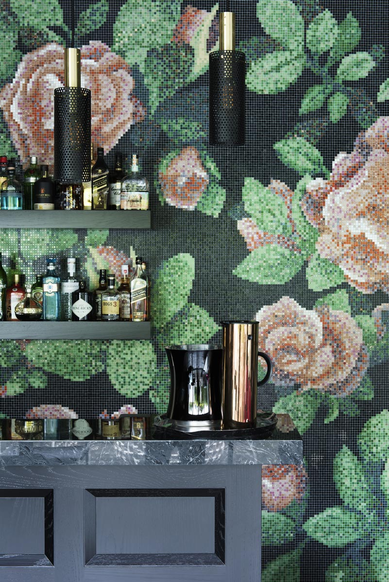 black bar with green floral tiled wall and alcohol on shelves