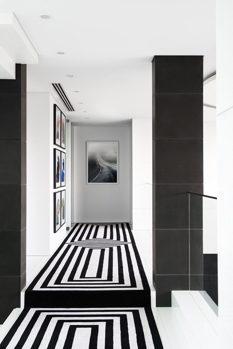 corridor with black and white stripe rug and paintings on the wall