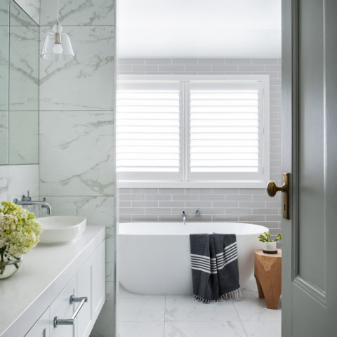 white marble tiled bathroom with white bath and black towel and white vanity