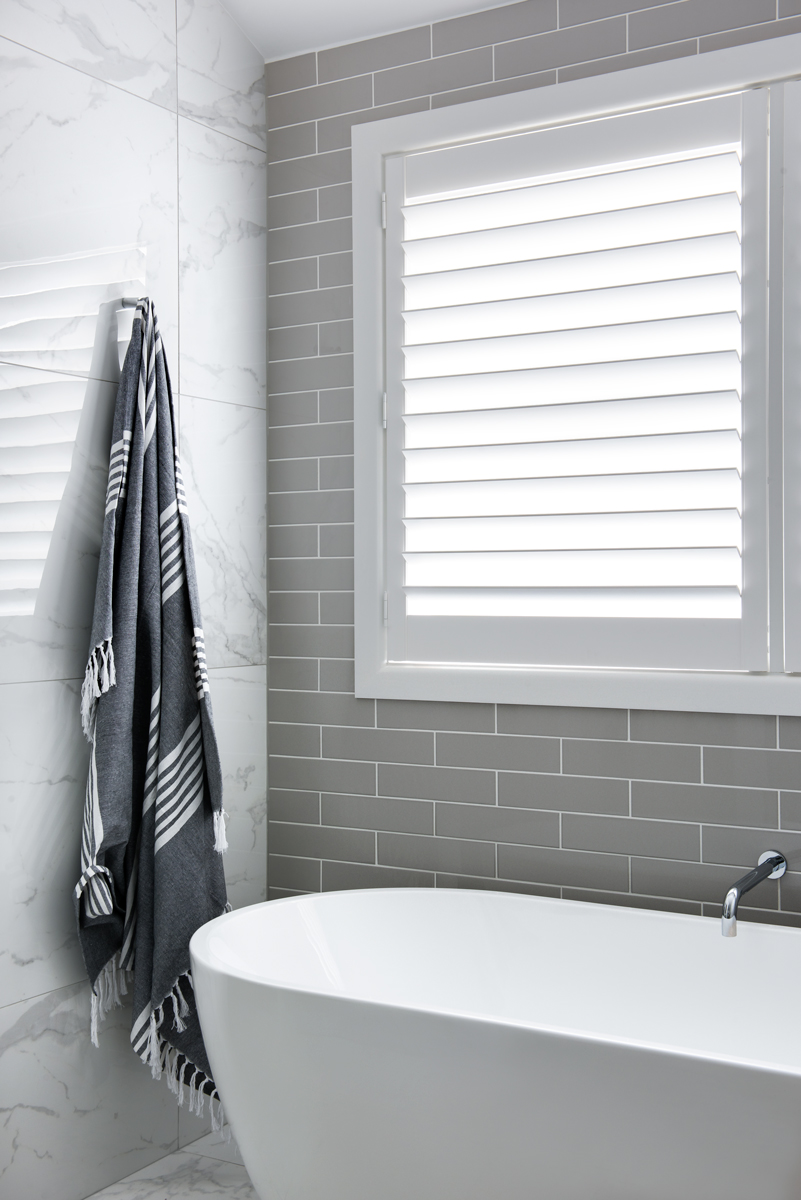 white marble tile wall next to grey brick wall with white blinds and bathrub and black towel