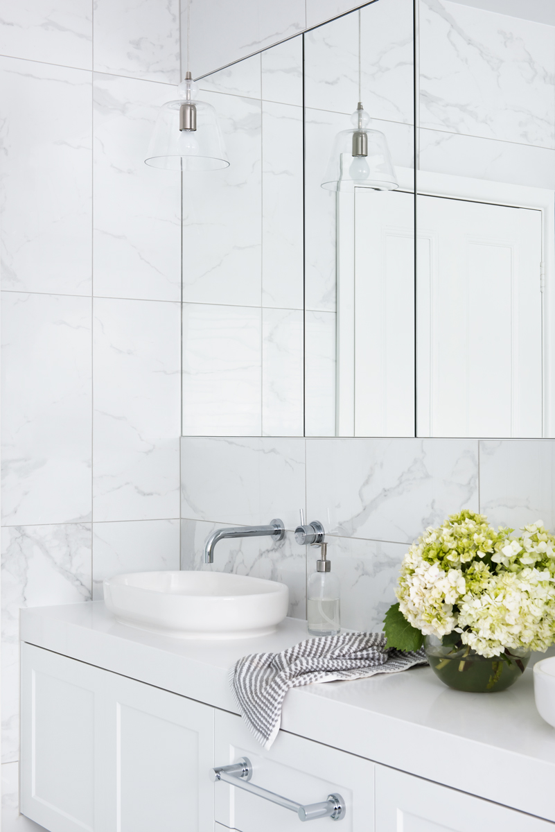 marble tiled bathroom walls with long mirrors and white vanity and sink with green flowers