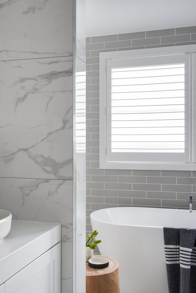 white marble tile walls with white bathtub and white blinds