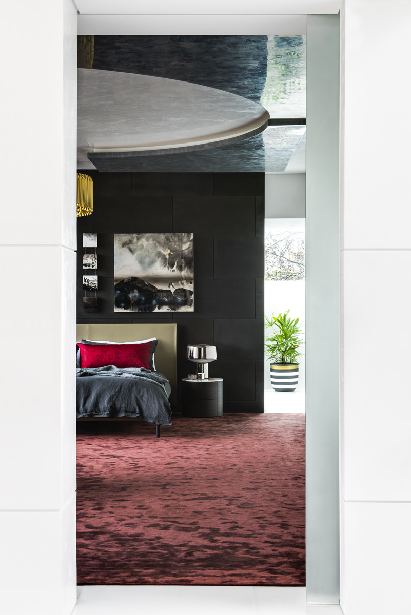 bedroom with red velvet carpet and dark walls with bed and lamp in the background