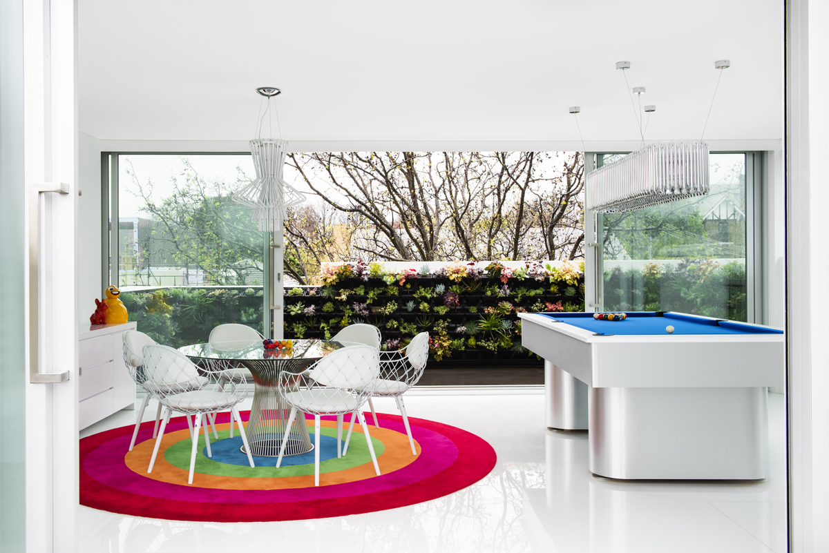 blue and silver pool table with rainbow rug and metal round table with white chairs