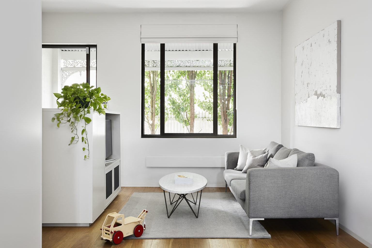 living room with windows and a grey couch and marble coffee table