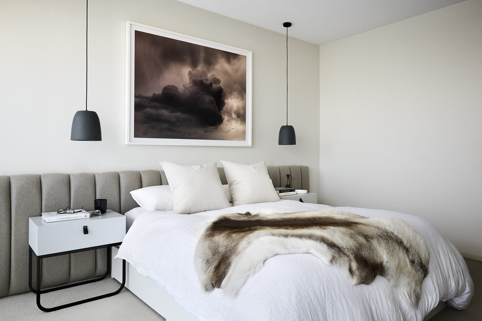 bedroom with a painting on the wall and a large bed and fur rug on top