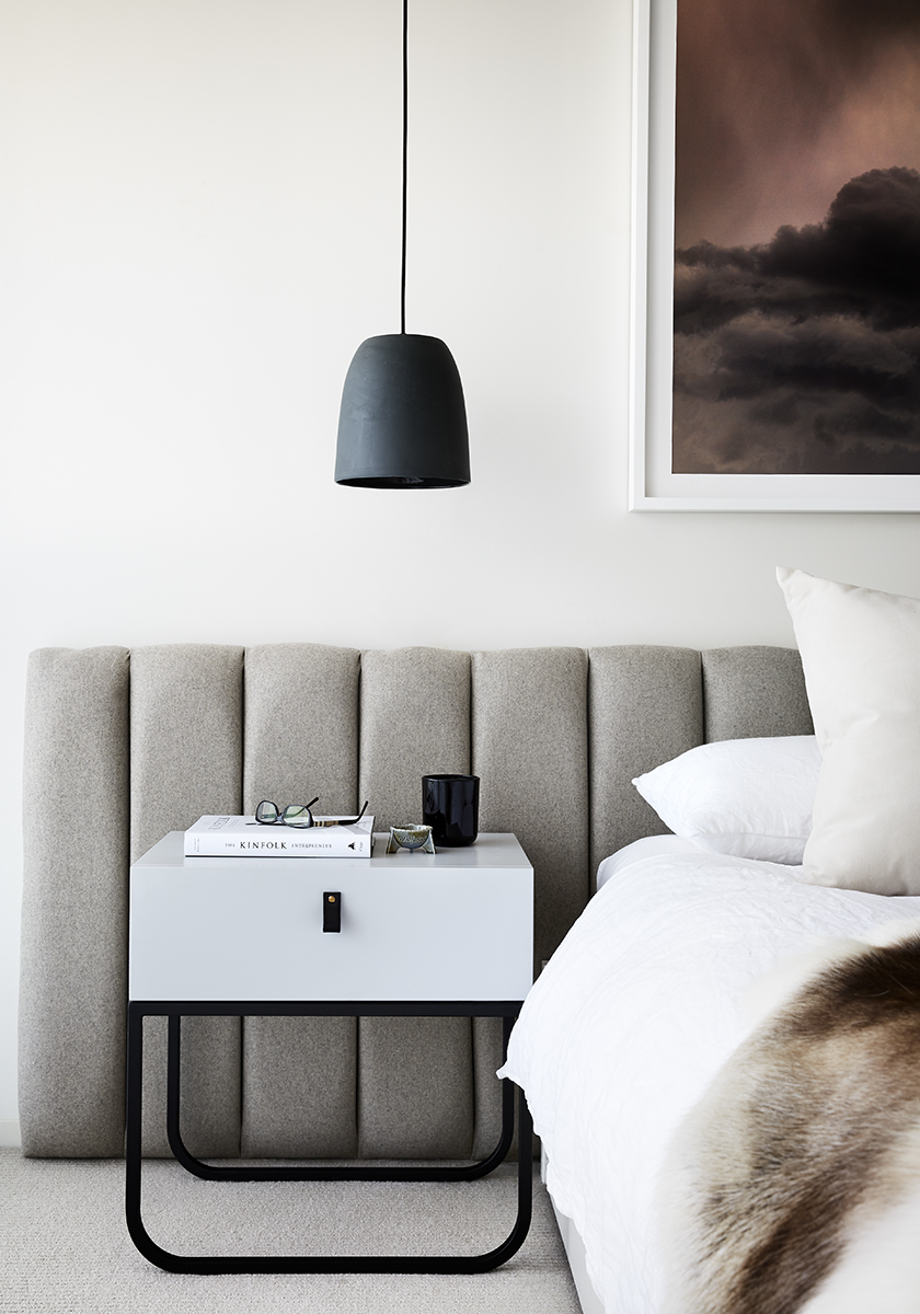 white minimalist bedside table with black hanging light