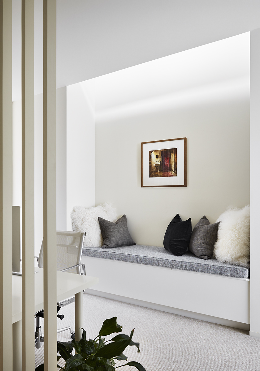 sitting nook with fluffy pillows and a painting