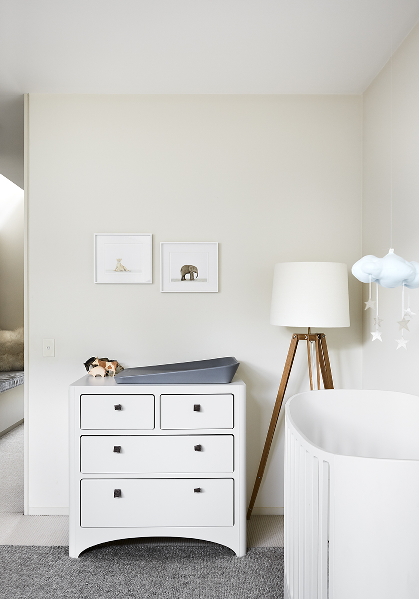 a child's room with a white dresser and cot and a tall lamp