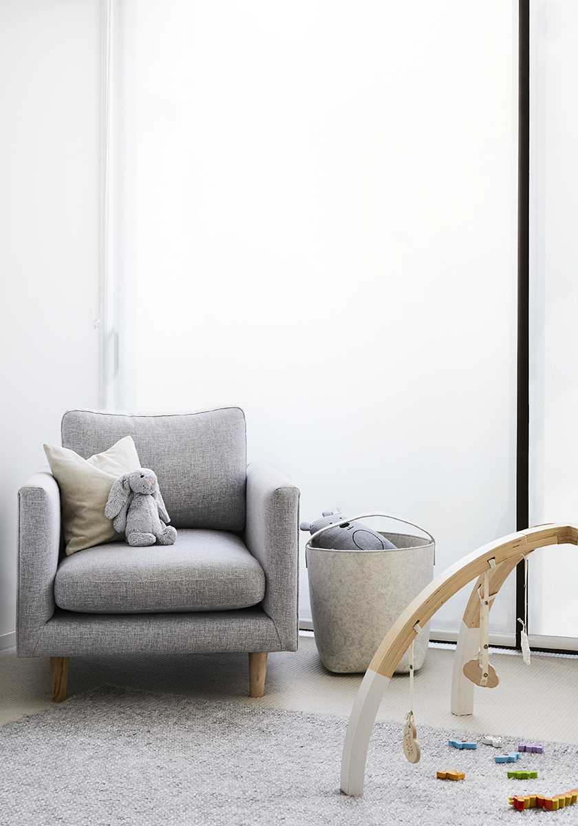 grey armchair with a soft toy rabbit and baby toys