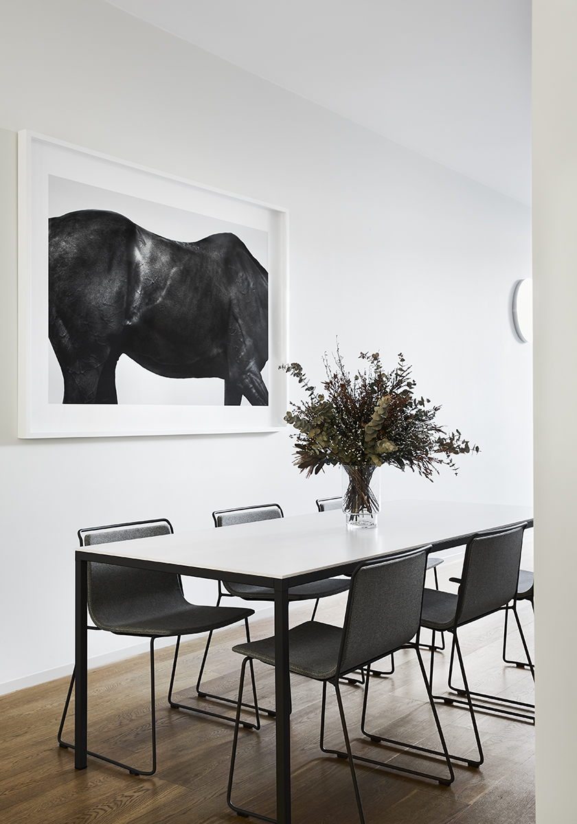 white dining table with black chairs and a painting on the wall