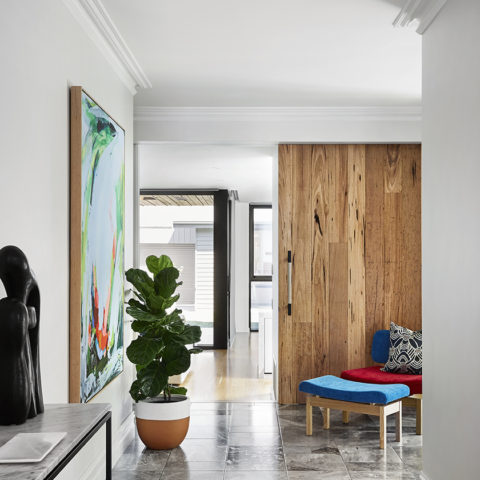 hallway with timber and stone floors and a pot plant next to a painting