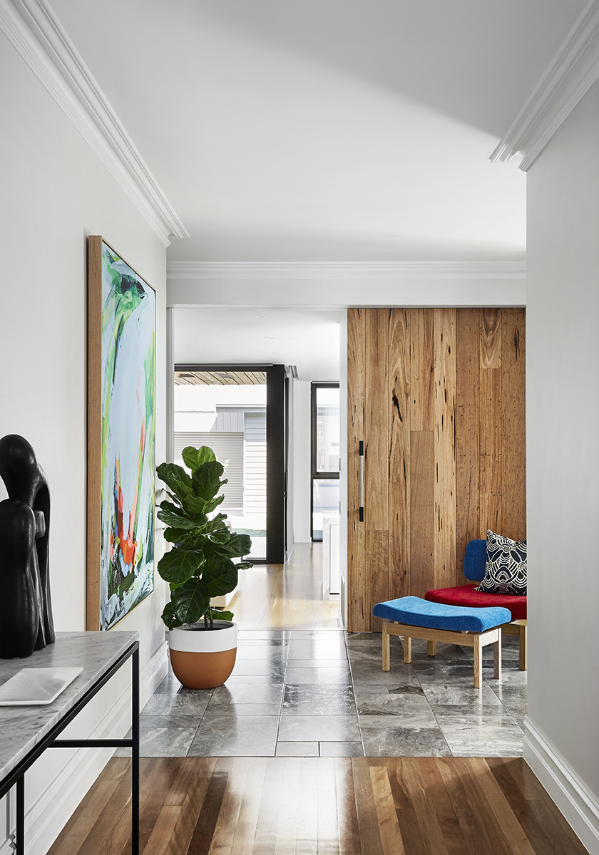 hallway with timber and stone floors with a pot plant and painting on the wall