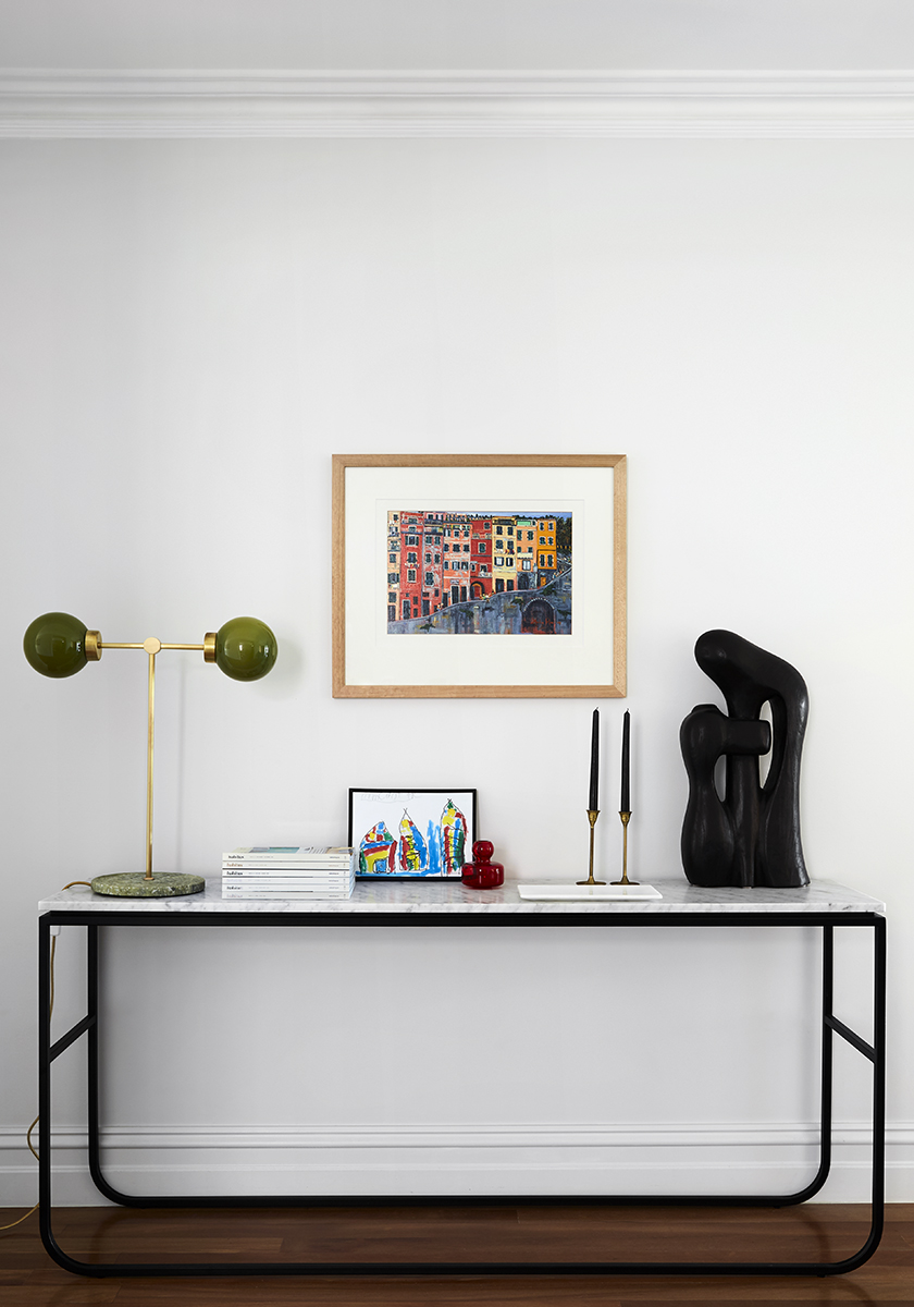marble side table with art and books on top with a painting on the wall