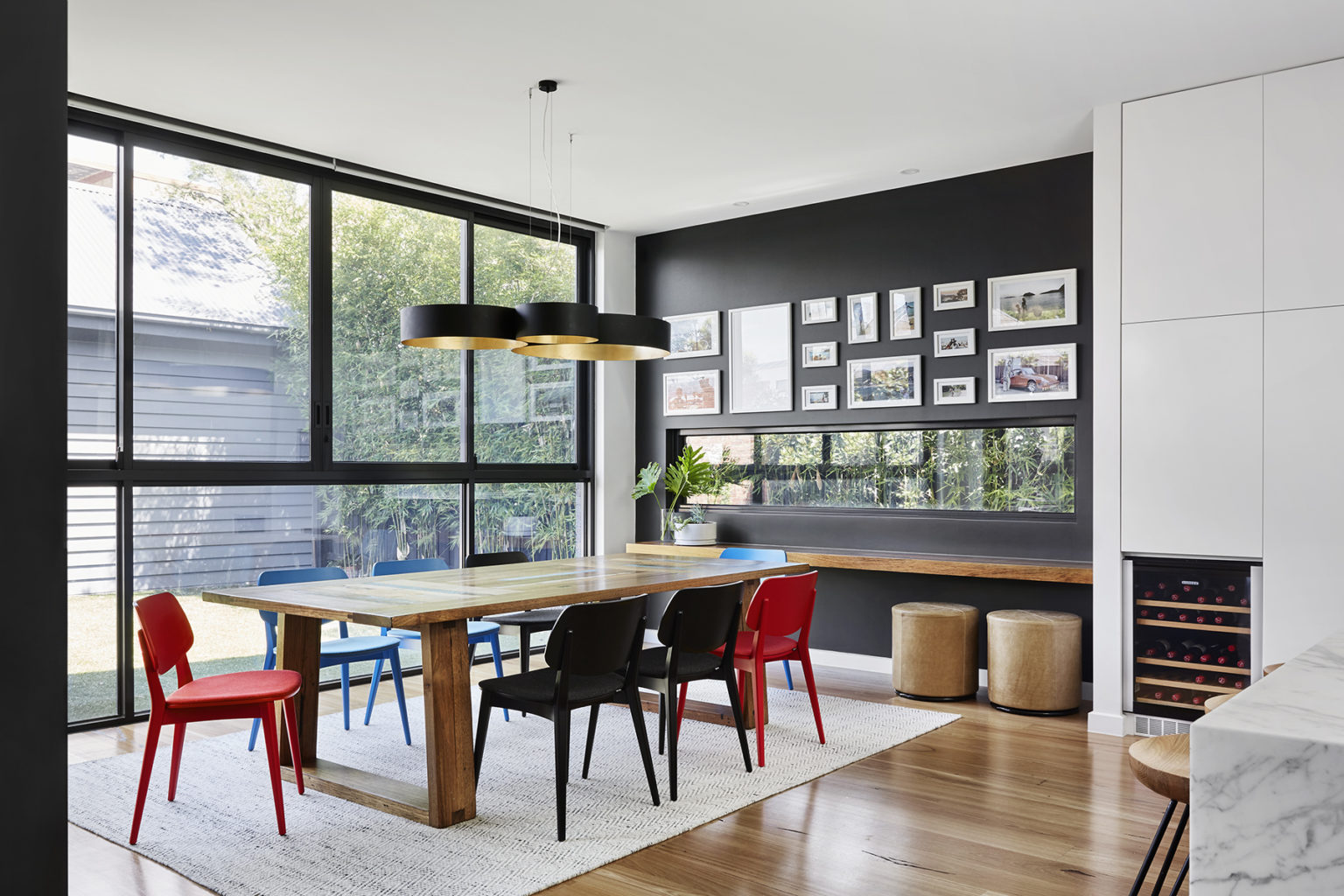 light filled dining room with wooden table and red black and blue chairs