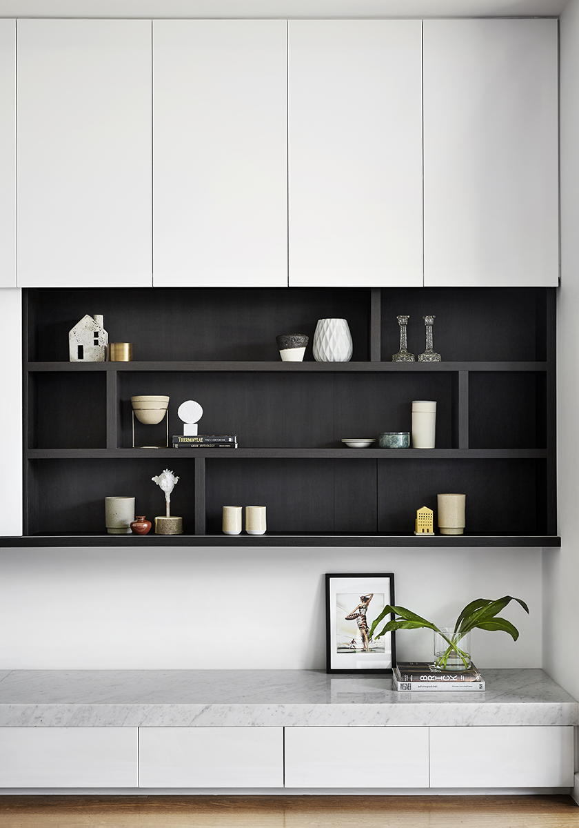white and black wall with built in shelving featuring candles and a plant