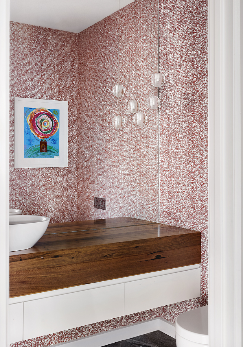 bathroom with pink wallpaper and a timber vanity