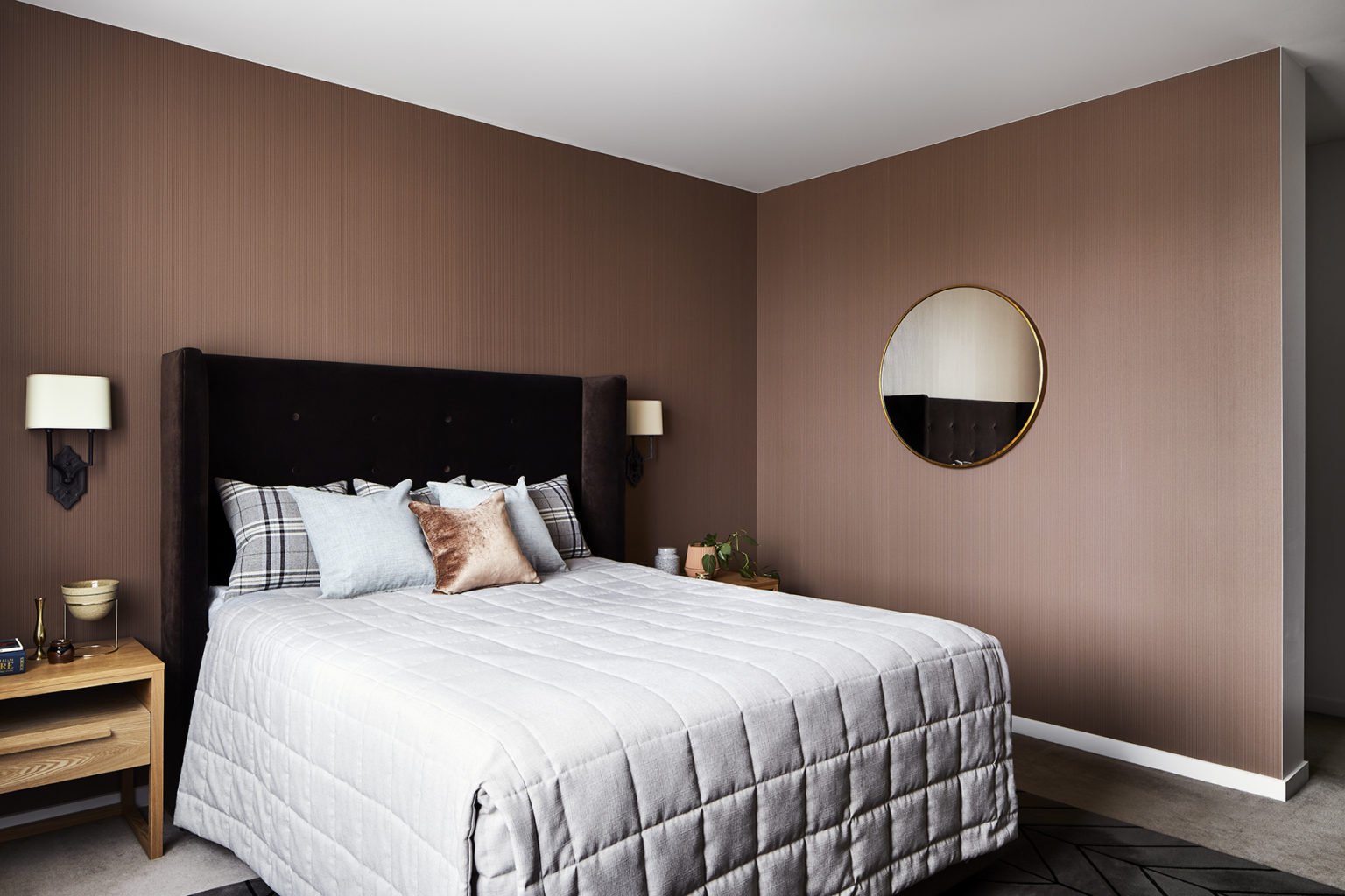 bedroom with grey quilted bed and round mirror on brown walls