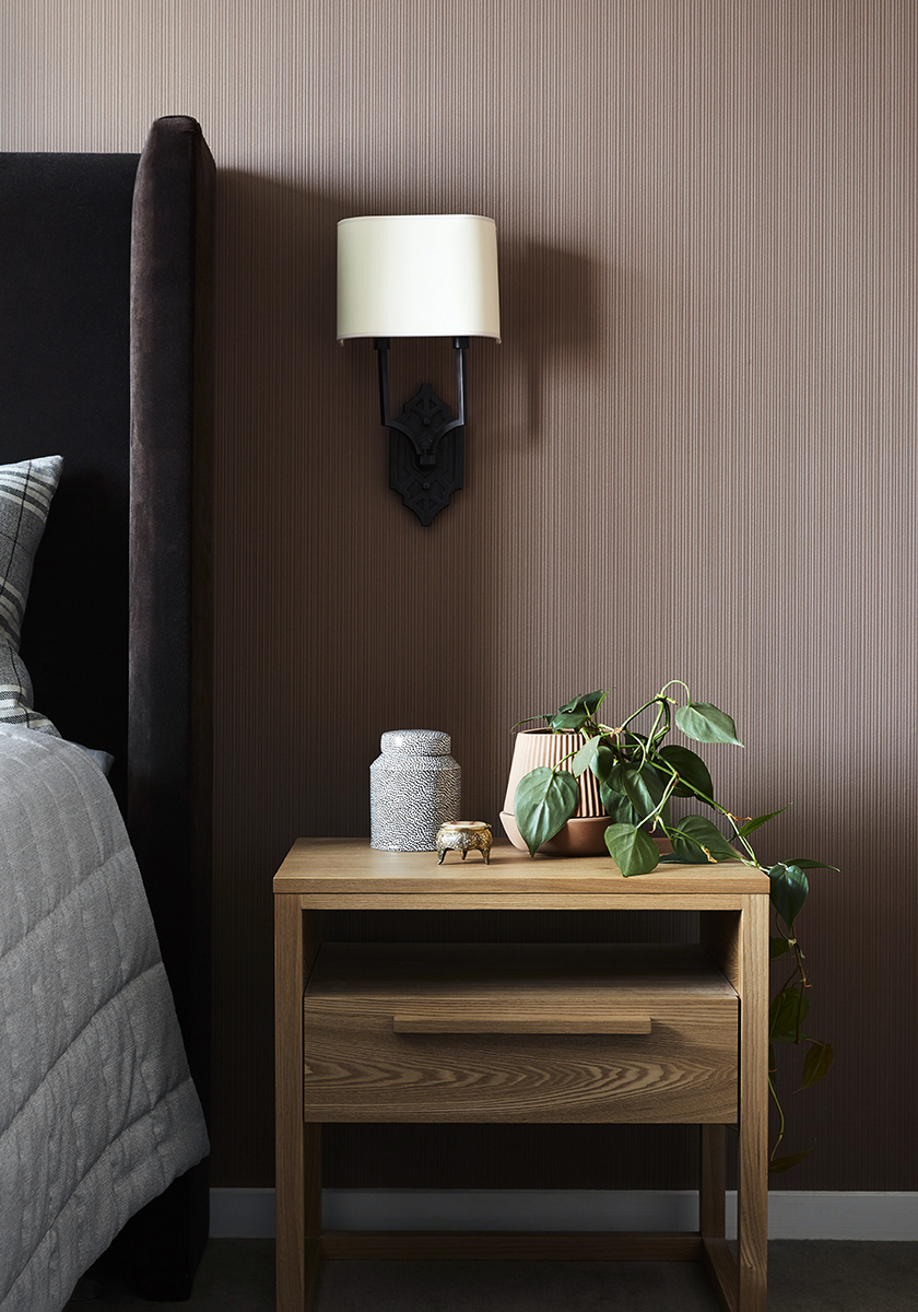 wooden bedside table with small plant and wall lamp