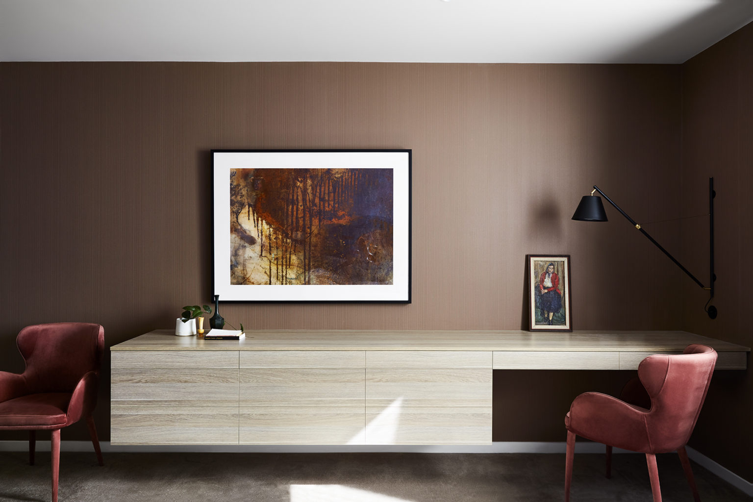sitting room with long light timber storage unit with red chairs and art on wall