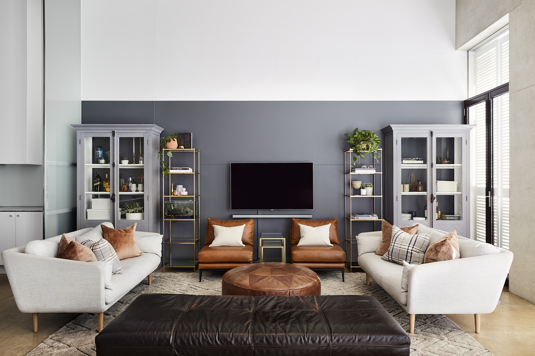 living room with cream couches and brown leather chairs and grey bookcases