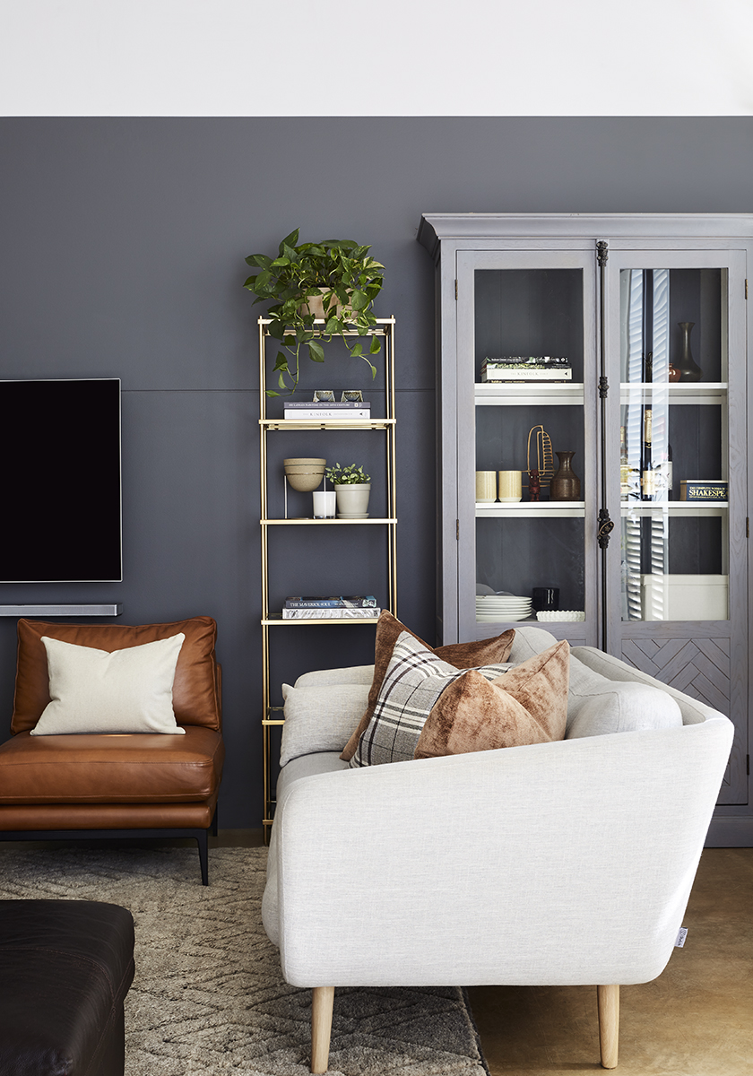 charcoal wall with gold bookshelf and a cream couch next to a brown leather chair