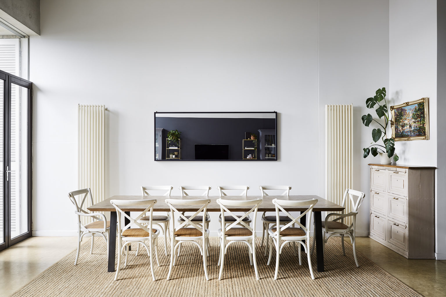 dining room with a long table and white wooden chairs on a straw rug