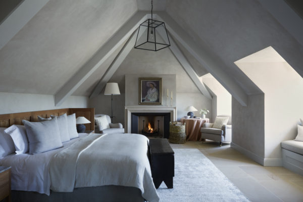 neutral bedroom with fireplace and hanging light