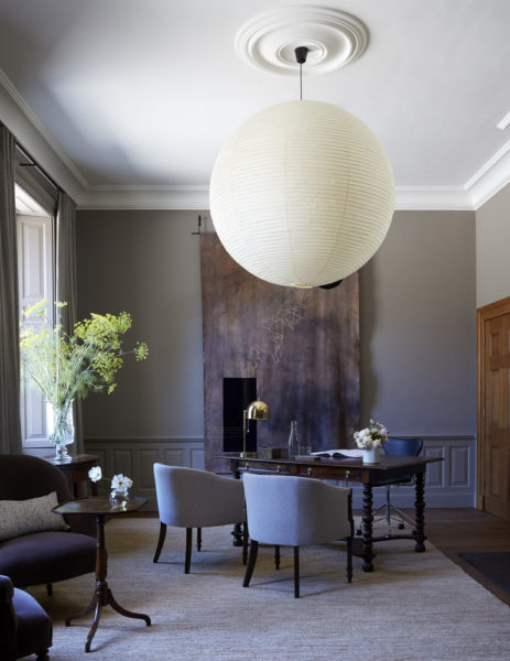 cool toned room with desk and chairs and a big circular hanging light