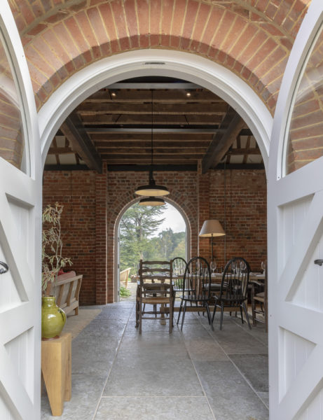 rounded doorway into a brick building with table and chairs and hanging lights