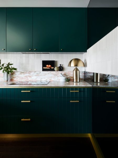 emerald green kitchen cupboards and gold lamp