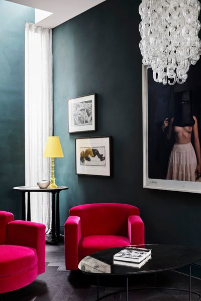 hot pink arm chairs in front of dark green walls and a black coffee table