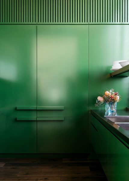 bright green kitchen cupboards with flowers in a vase