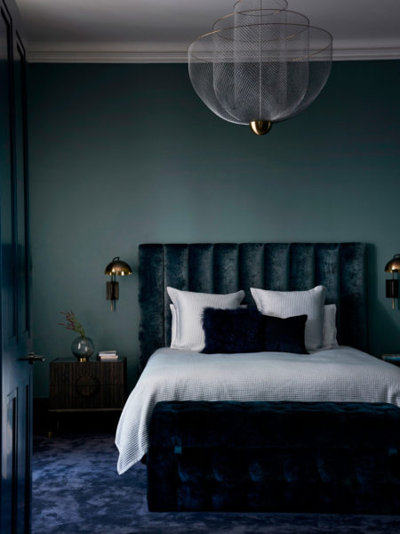 double bed against emerald green bedroom wall blue velvet carpet
