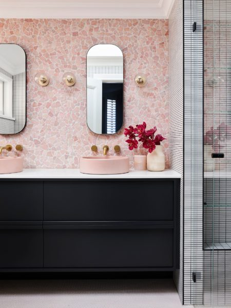 bathroom with pink tiled walls and a black vanity and pink flowers