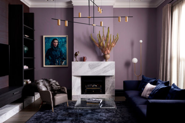 living room with a fireplace against a purple wall and a dark blue couch