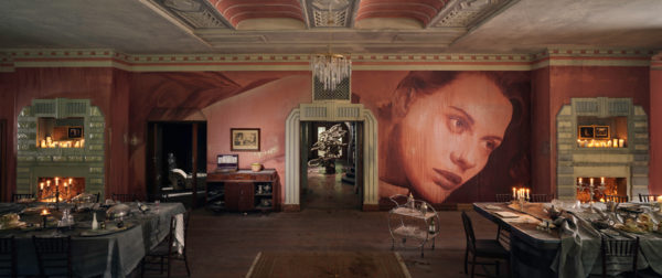 big room with woman painted on red wall with fireplaces