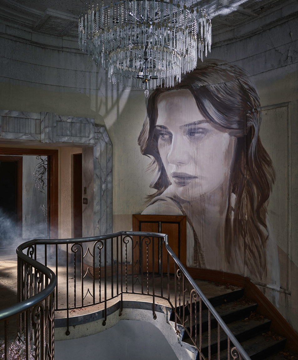 staircase with a woman painted on the wall and a chandelier hanging from the ceiling