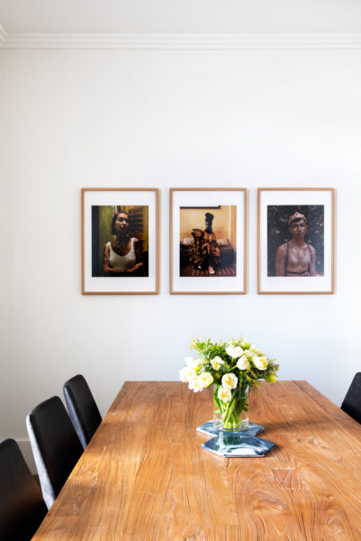 wooden table with three paintings on the wall