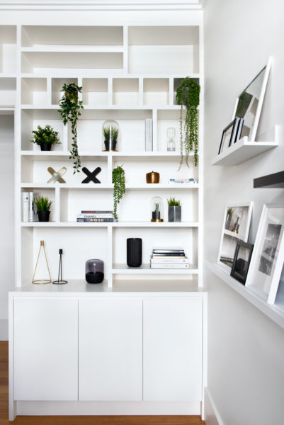 white bookshelf with books and plants hanging
