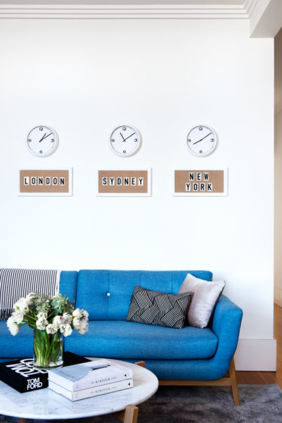 blue couch with coffee table and world clocks on the wall