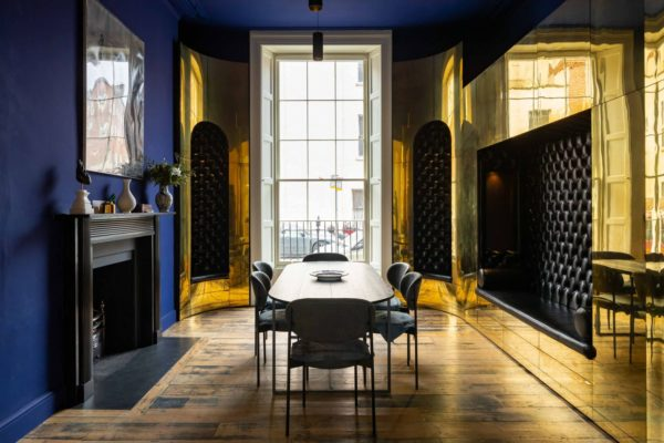 deep purrple and shiny gold walls with a big window and dining table and chairs