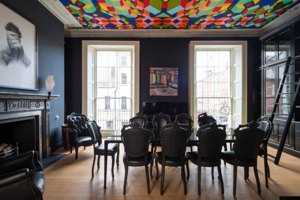moody and eclectic dining room with colourful roof and black table and chairs