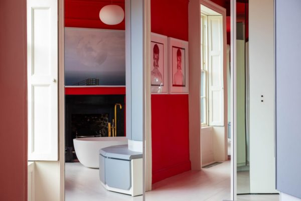 red walls with a white bath and paintings on the walls