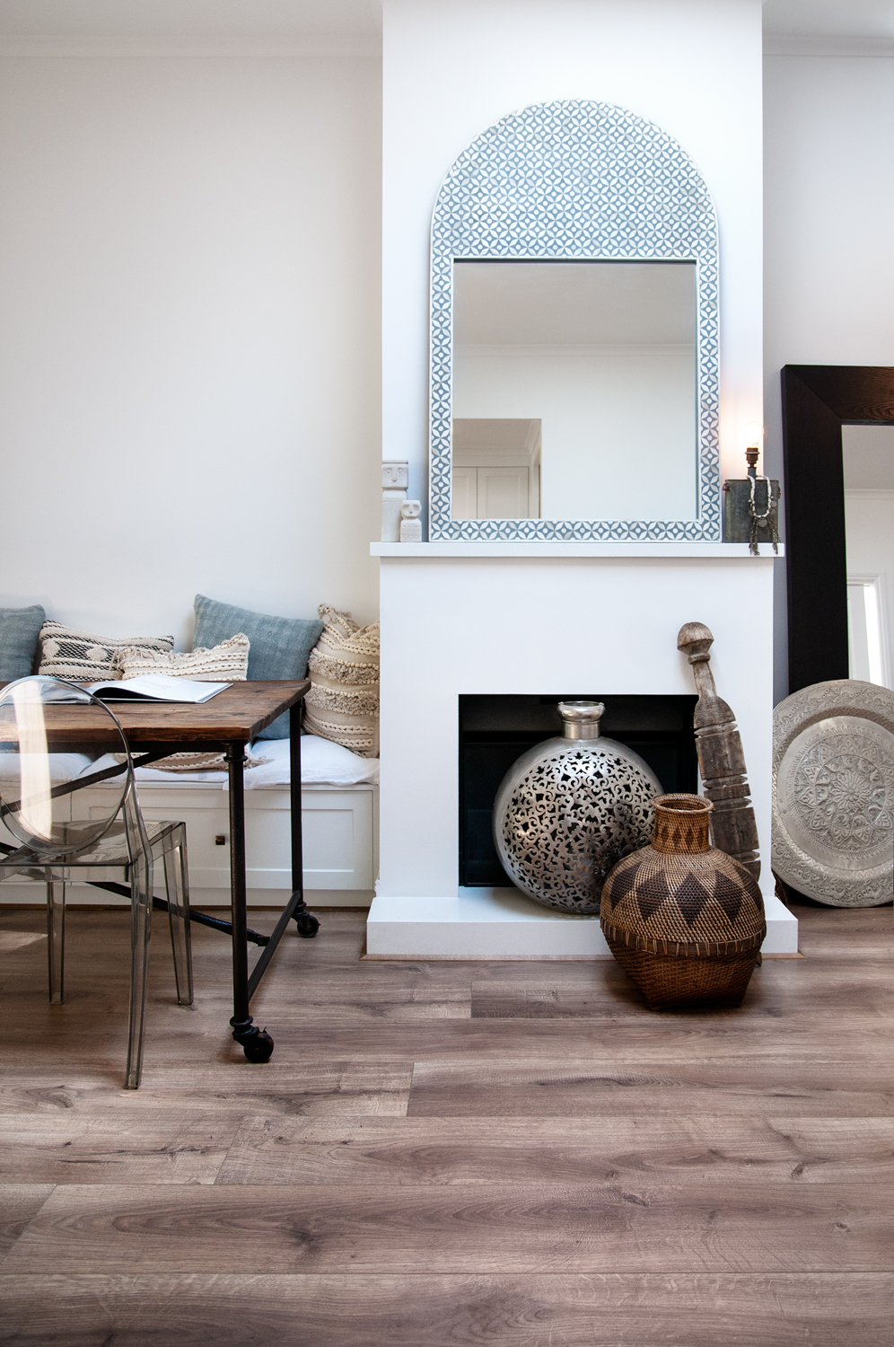 White fireplace with a mediterranean style mirror on the mantlepiece and an array of decorative pots on the floor