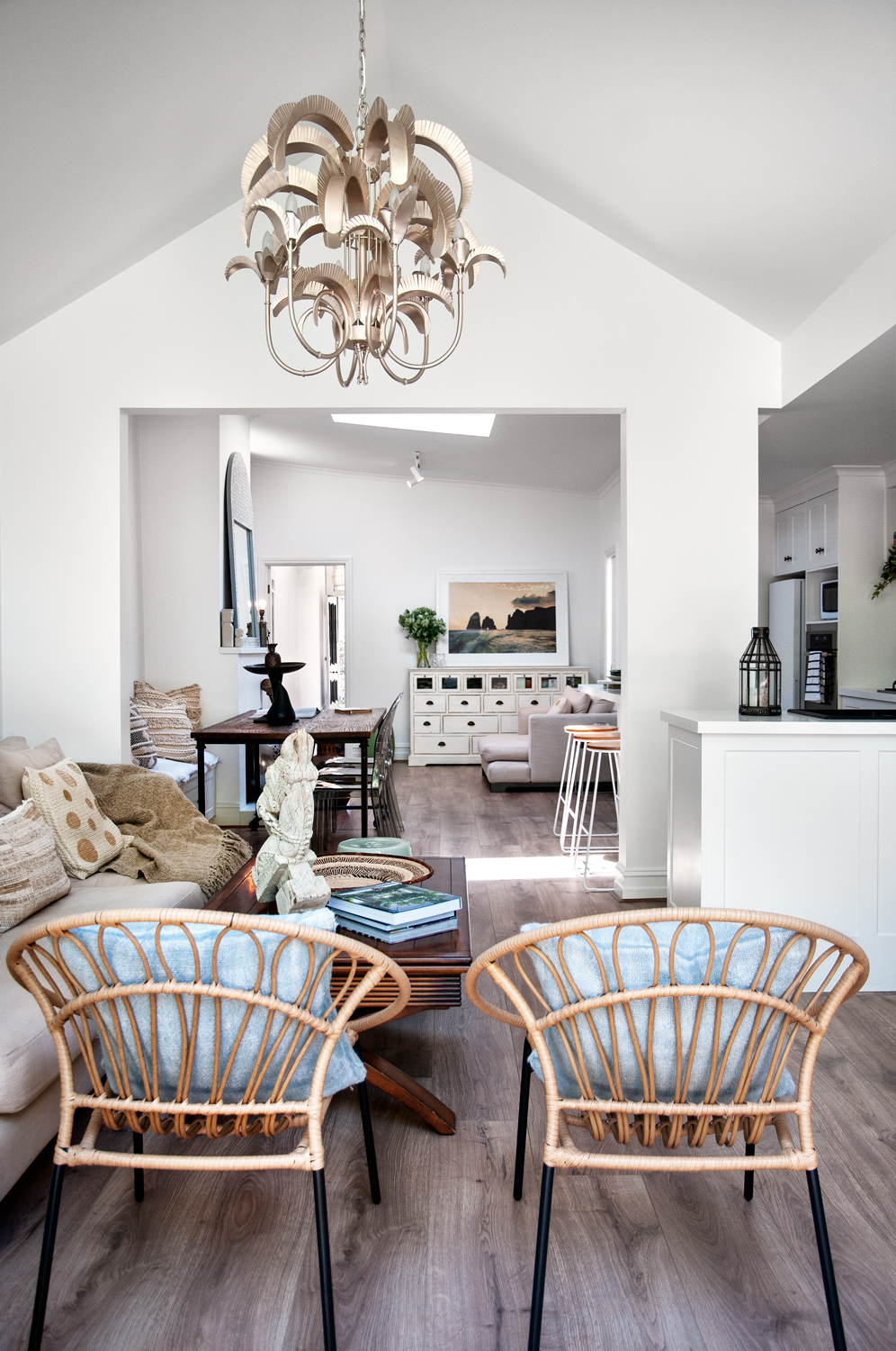 Two rattan chairs in the living room with an intricate hanging feature light