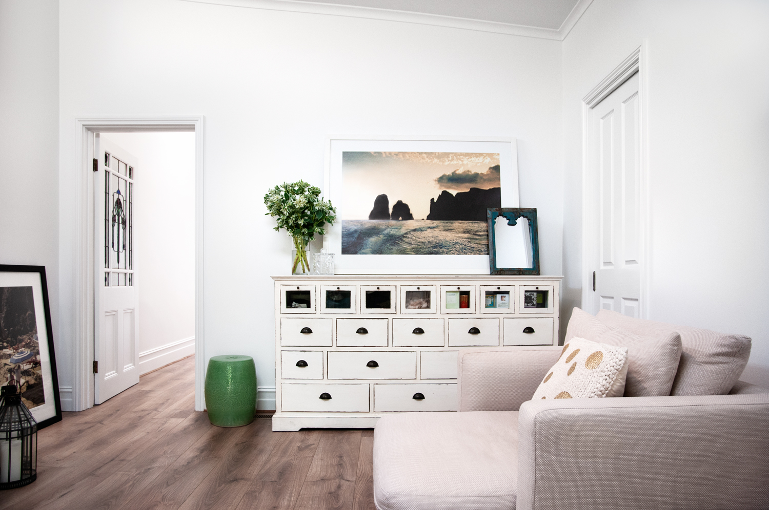 Bright sitting room with a cream set of drawers and a baby pink armchair