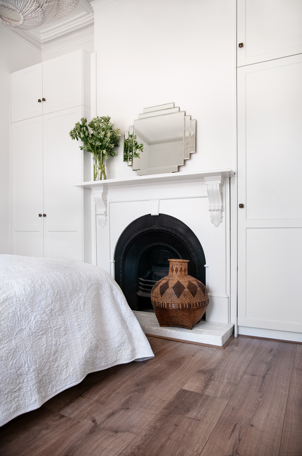 Bedroom with white fireplace with a mirror on the mantlepiece and a brown pot on the floor